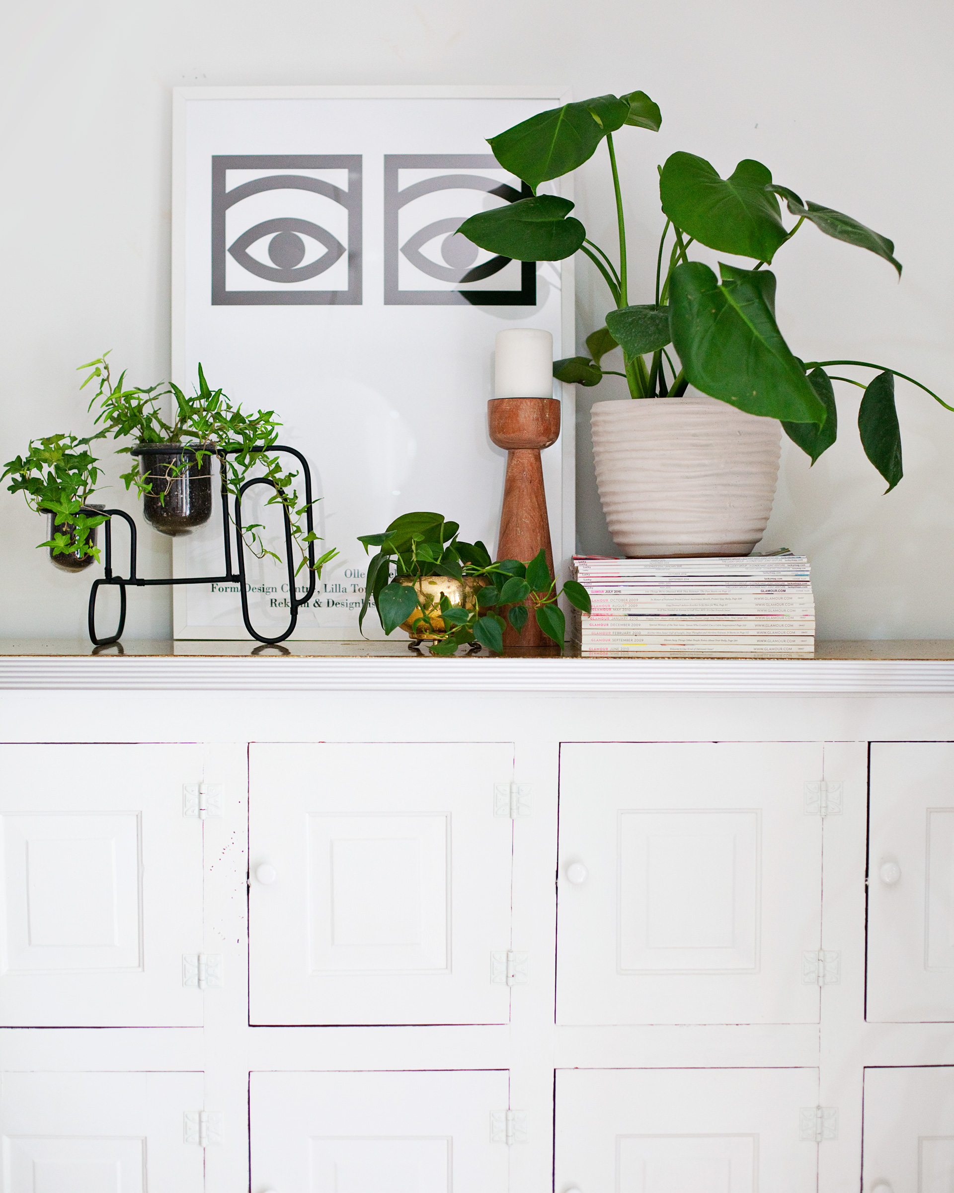 sideboard vignette with plants and candle holder